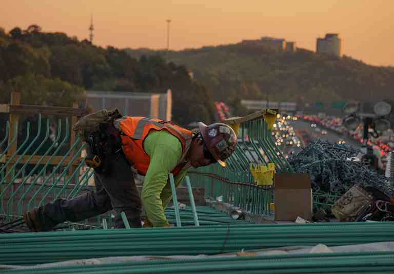 Man working on top of a building being built. Alliance United workplace safety services in New England.