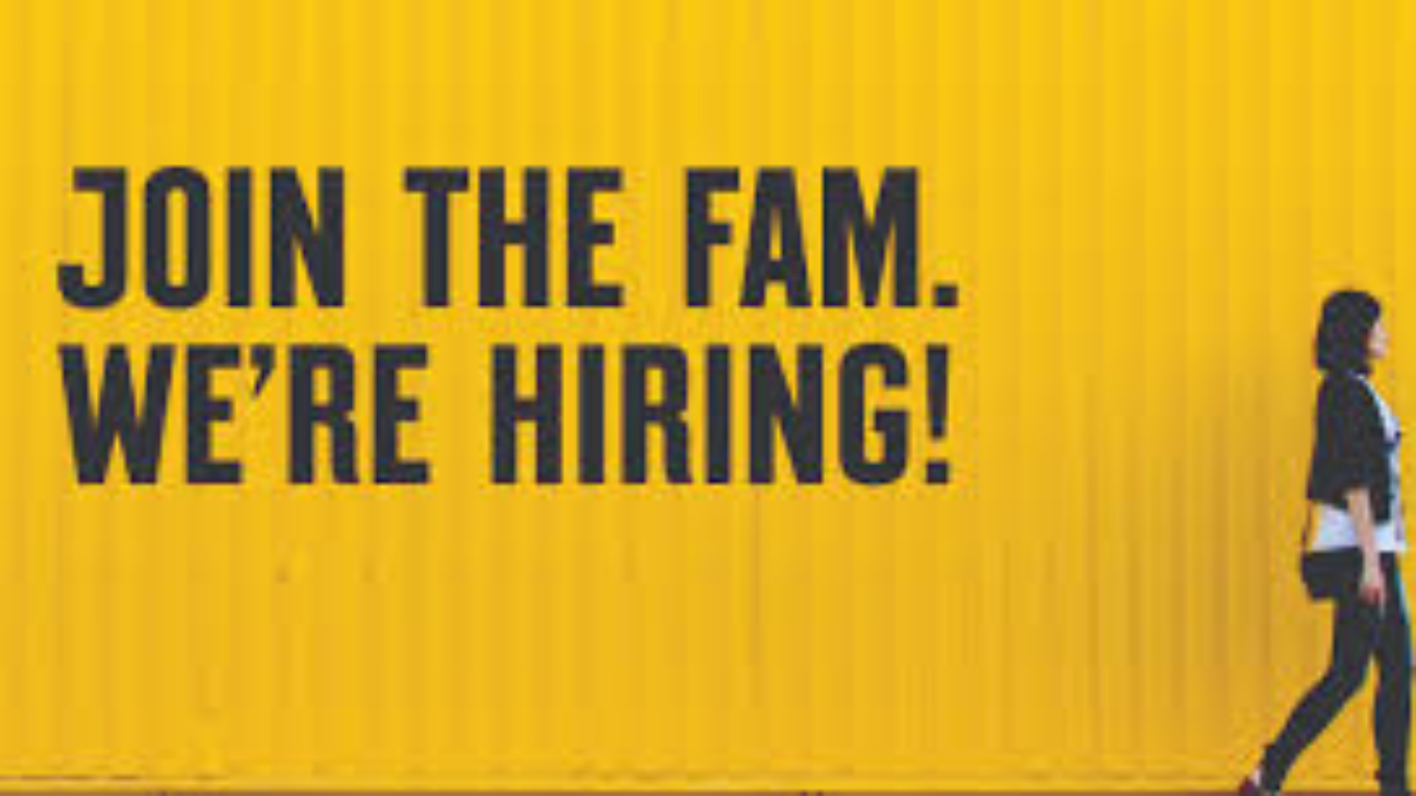 """a yellow image with black text stating """"join the fam. we're hiring!"""" with a woman walking beside the image."""
