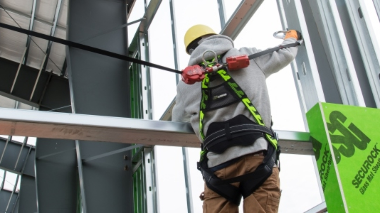 Worker using fall protection gear as a safety precaution he learned in em 385 training