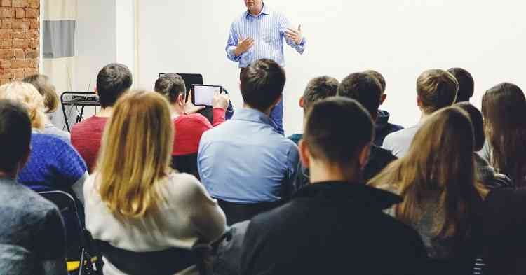 Adult students listen to professor's lecture in small class room.