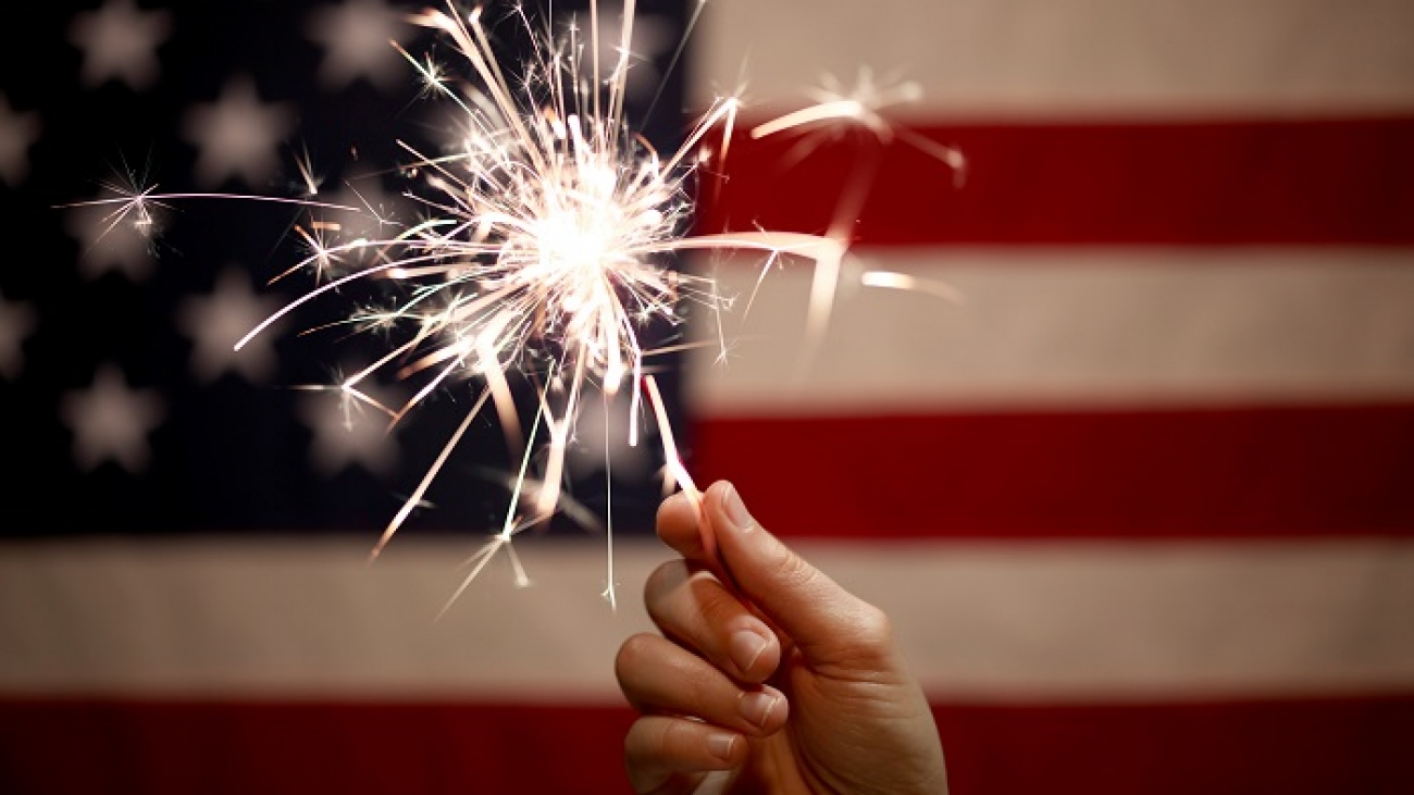 Hand holding lit sparkler in front of the American Flag for 4th of July celebration