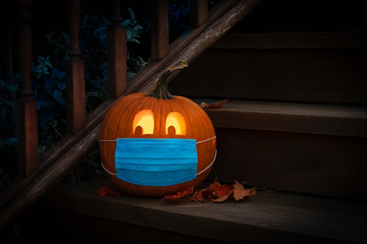 Lighted Carved Jack-o-Lantern dressed up for Halloween with COVID Pandemic face mask