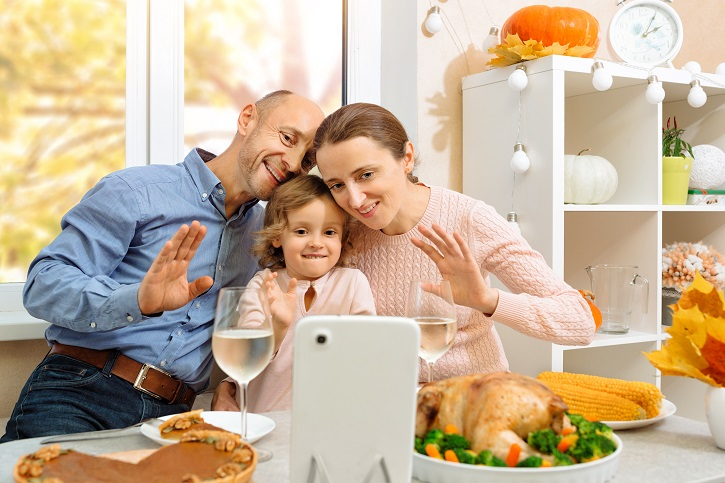 A happy family have a thanksgiving dinner and sends a video greeting to their parents by internet.
